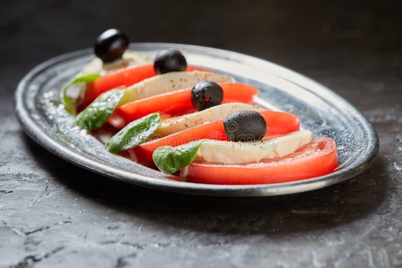De salade van Caprese Tomaat en Mozarellaplakken, Basilicum stock fotografie
