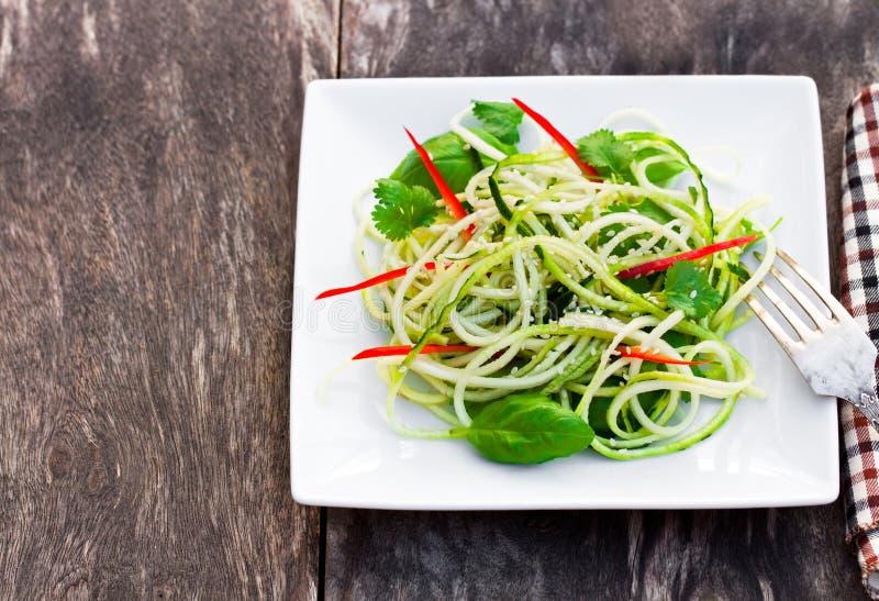 De salade van de courgettespaghetti met basilicum en paprica op geregeld plat stock fotografie