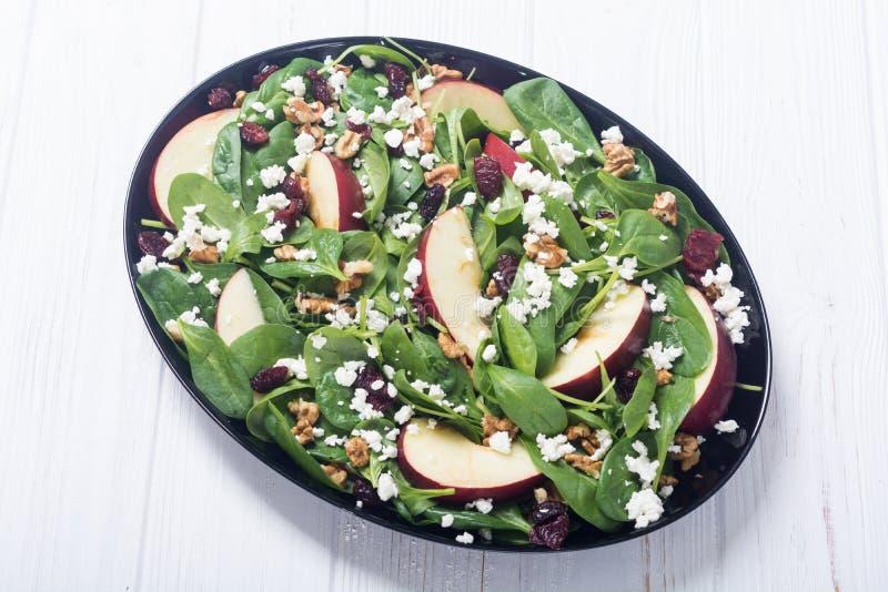 De salade van de de herfstspinazie met appelkaas, okkernoot en droge Amerikaanse veenbes Gezond vegetarisch voedsel stock afbeeldingen