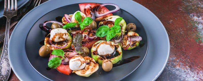 De salade van de voedselbanner met geroosterde groenten, mozarella, olijven, rode ui, basilicum en balsemieke saus op een roestac stock afbeelding