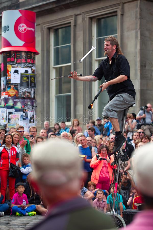 De saldi van de straatentertainer op unicycle en jongleert met met divers royalty-vrije stock foto