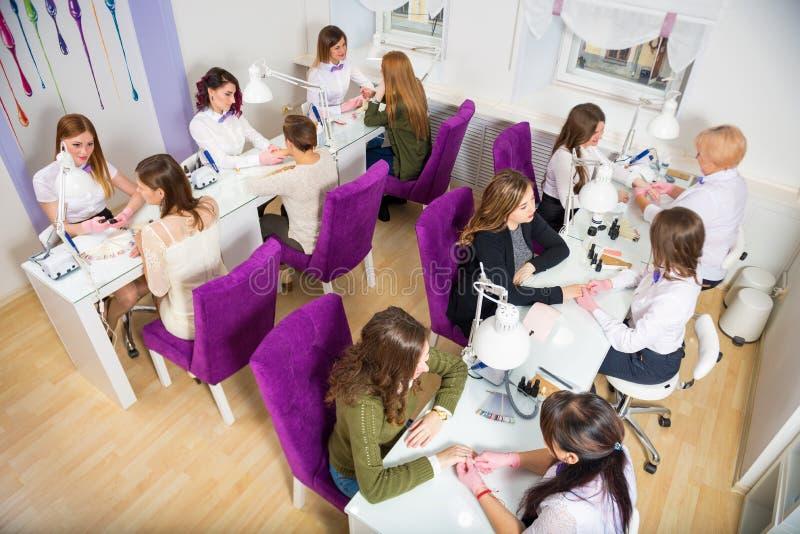 De salon van de schoonheid Vrouwen die manicure doen Manicurespecialisten in de werkplaats royalty-vrije stock foto