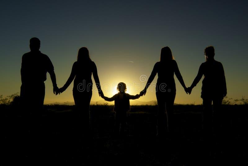 De Samenhorigheid en de eenheid van de familie in Zonsondergang stock foto