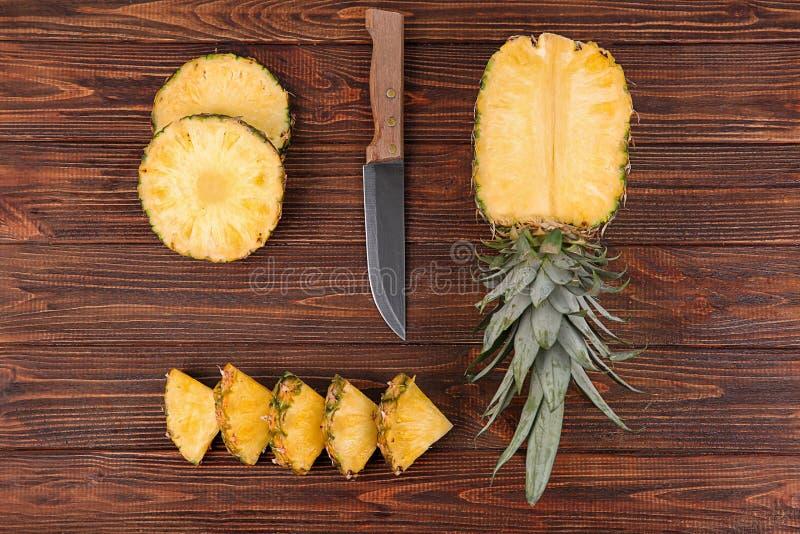 De samenstelling met mes en gesneden ananas op houten achtergrond, vlakte lag stock afbeeldingen