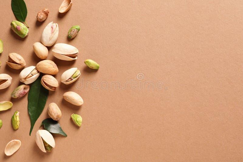 De samenstelling met organische pistachenoten op vlakke kleurenachtergrond, legt royalty-vrije stock fotografie