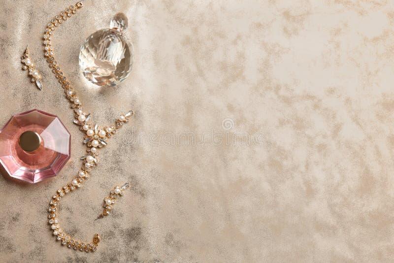 De samenstelling met parfumflessen en juwelen op vlakke stof, legt stock afbeelding