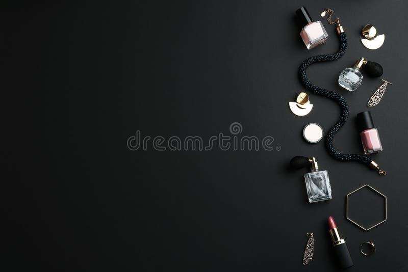 De samenstelling met parfumflessen, schoonheidsmiddelen en juwelen op zwarte vlakke achtergrond, legt royalty-vrije stock afbeelding