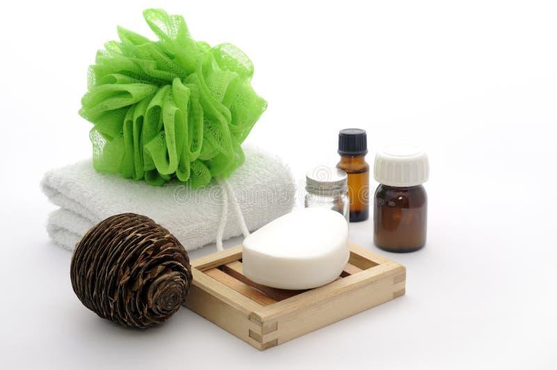 De samenstelling van de badkamers met zeep, olie, handdoek, spons stock fotografie