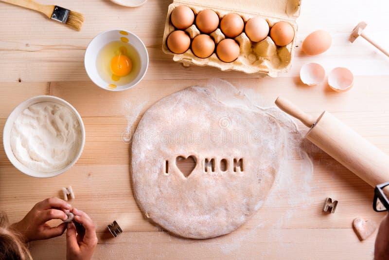 De samenstelling van de moedersdag Het mengsel van het chocoladekoekje, het bakken de vormen en het snoepje versieren op witte ac royalty-vrije stock afbeelding