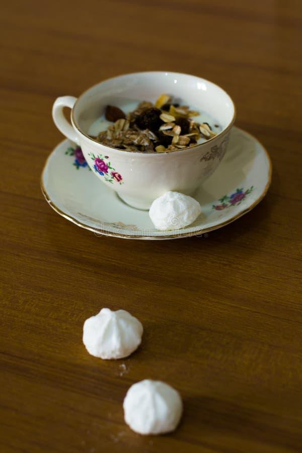 De samenstelling van een een porseleinkop en schotel vulde met yoghurt en muesli en drie witte snoepjes royalty-vrije stock afbeeldingen