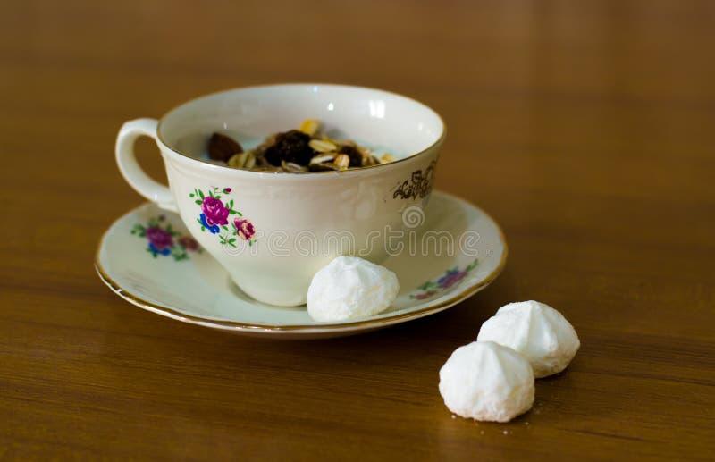 De samenstelling van een een porseleinkop en schotel vulde met yoghurt en muesli en drie witte snoepjes stock afbeeldingen