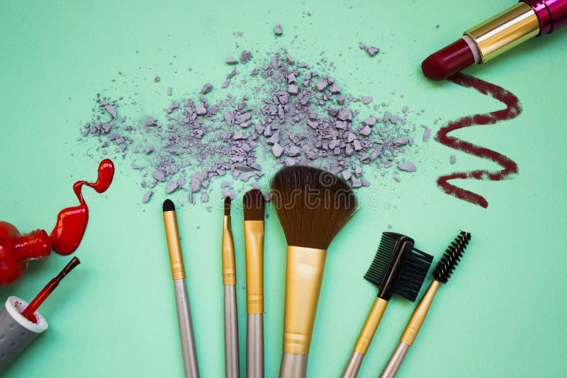 De samenstelling van een reeks van make-up op een turkooise achtergrond met schaduwen en nagellak royalty-vrije stock afbeeldingen