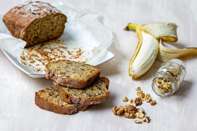 De samenstelling van het banaanbrood met okkernoten, banaanfruit en glas melk stock afbeeldingen