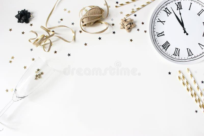 De samenstelling van het nieuwjaarstilleven met gouden confettiensterren, wijnglas, het drinken stro en klokplaat Partij stock afbeeldingen