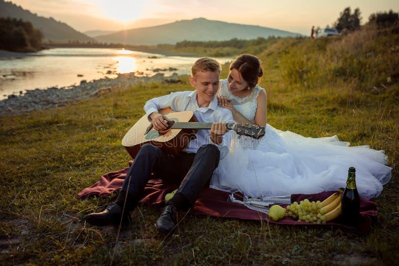 De samenstelling van de huwelijkspicknick op de rivierbank tijdens de zonsondergang De glimlachende bruidegom speelt de gitaar te stock afbeeldingen