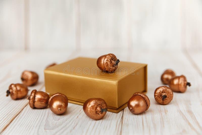 De samenstelling van Kerstmis Gouden huidige doos en gouden eikels Witte Houten lijst stock foto's