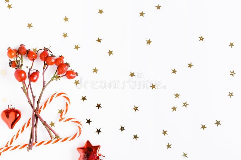 De samenstelling van Kerstmis Rode rozebottelbessen op een witte achtergrond en gouden sterren Kerstmis, nieuw jaar, de wintercon royalty-vrije stock afbeeldingen