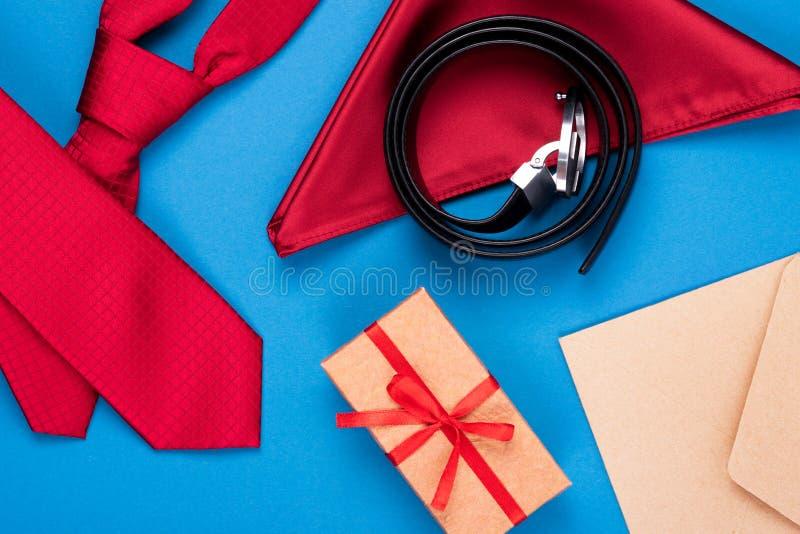 De samenstelling van rode halsband, in eigen zak steekt vierkant, giftdoos, ambachtenvelop en riem op blauwe cyaanachtergrond Mod royalty-vrije stock foto's