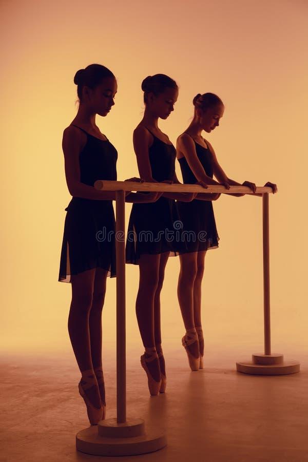 De samenstelling van silhouetten van drie jonge dansers in ballet stelt op een oranje achtergrond royalty-vrije stock afbeeldingen