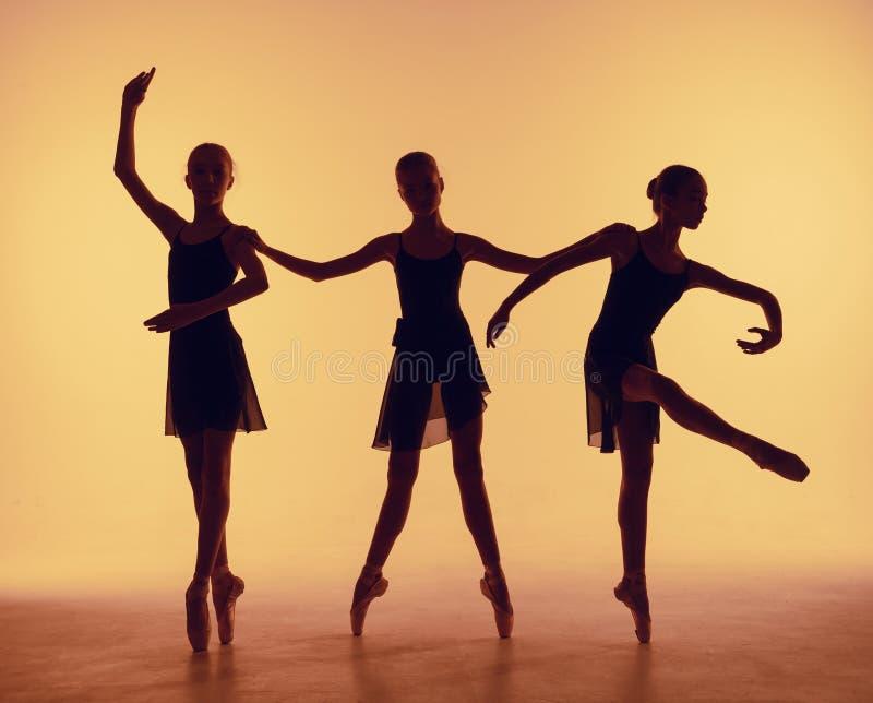 De samenstelling van silhouetten van drie jonge dansers in ballet stelt op een oranje achtergrond stock foto's