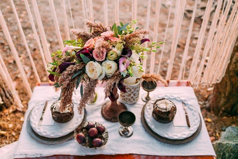 De samenstelling van verschillende bloemen die zich op gediende lijst op het gebied van huwelijkspartij bevinden Bloemenregeling royalty-vrije stock fotografie