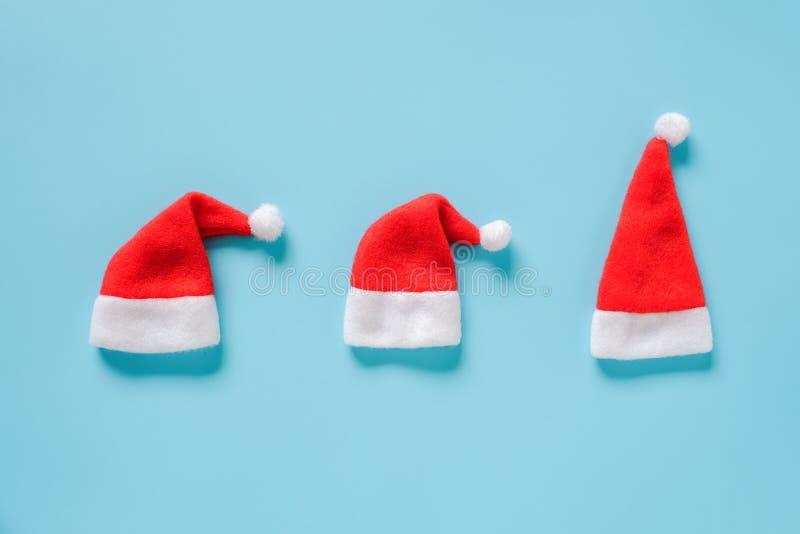 De samenstelling van de de wintervakantie Drie rode Santa Claus Hats op blauwe achtergrond Vlakte van de de Lay-out legt de Hoogs stock fotografie