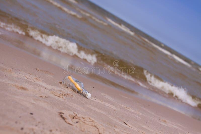 De samenstellingen van het strand. Botlle die door het water wordt gebracht stock afbeeldingen