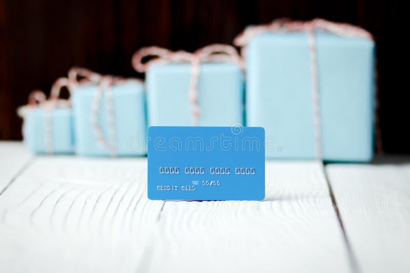 De samenstellings blauwe creditcard van het Kerstmis nieuwe jaar met giften op bedelaars stock afbeeldingen
