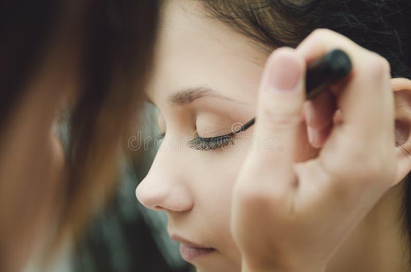 De samenstellingsmeester schildert de ogen van het meisje Maakt make-up, close-up royalty-vrije stock foto's