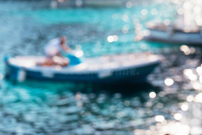 De samenvatting defocused achtergrond Onscherp blauw water met de boot in zonlicht royalty-vrije stock foto's