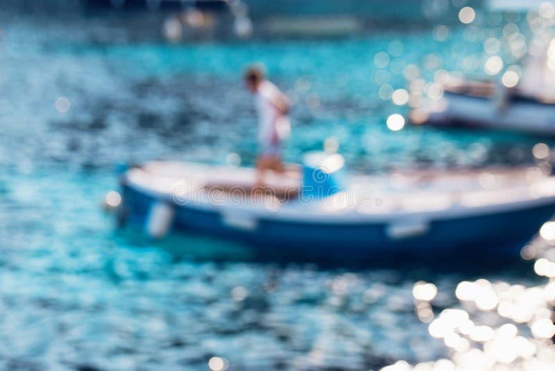 De samenvatting defocused achtergrond Onscherp blauw water met de boot in zonlicht royalty-vrije stock foto