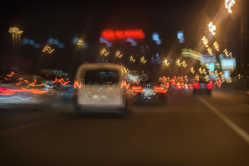 De samenvatting vertroebelde bewegende witte auto en snel drijfverkeer bij nacht in stad, heldere stoplichten royalty-vrije stock foto