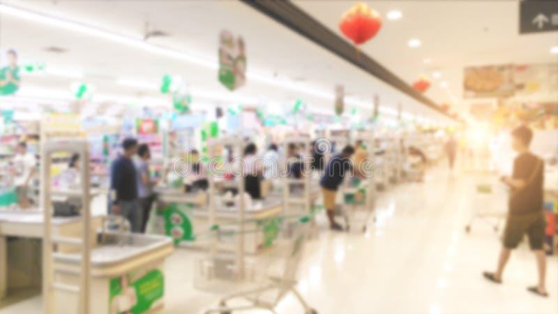 De samenvatting vertroebelde controlebureau in supermarkt voor achtergrond, rij van kassiersteller met klant binnen markt stock afbeeldingen
