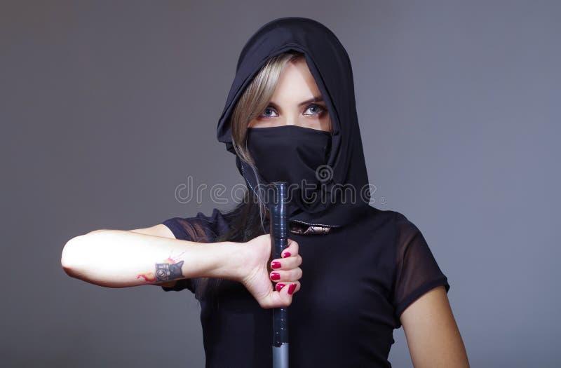 De samoeraienvrouw kleedde zich in zwarte met de aanpassing van sluier die gezicht behandelen, die hand op zwaard houden die came royalty-vrije stock foto