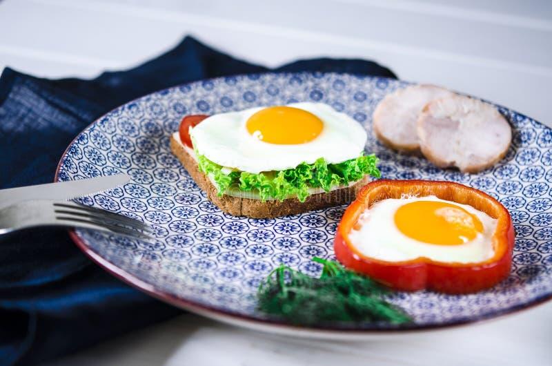 De sandwich met ei, ham, kaas, toost en saladebladeren ligt op een plaat met tomaat en dille stock afbeeldingen