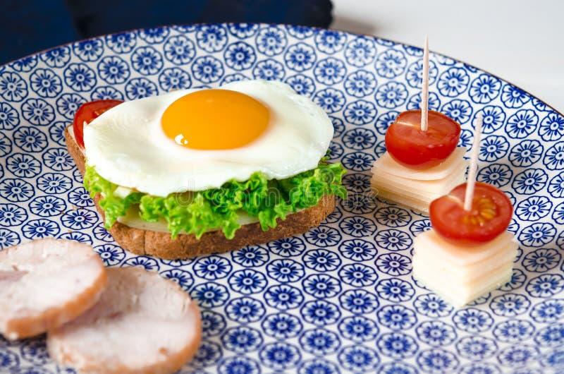De sandwich met ei, ham, kaas, toost en saladebladeren ligt op een plaat met tomaat en dille royalty-vrije stock fotografie