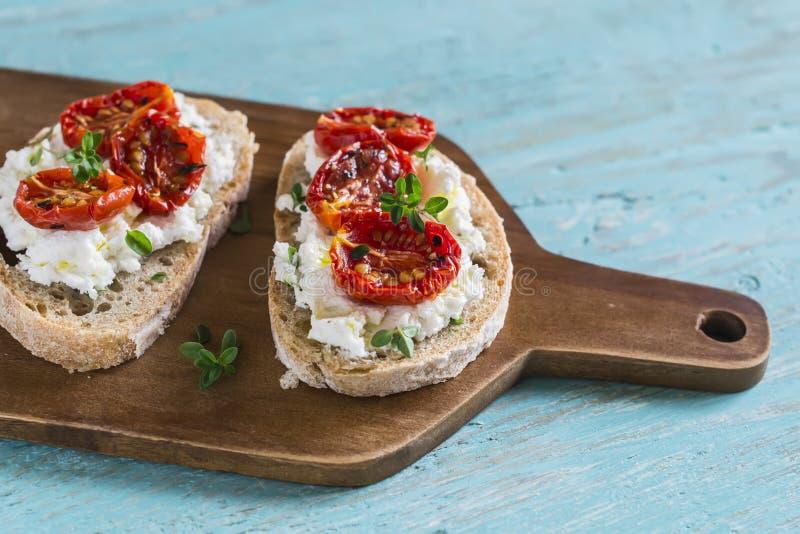 De sandwich met geitkaas, in de zon gedroogde tomaten en thyme, diende op de Raad royalty-vrije stock fotografie