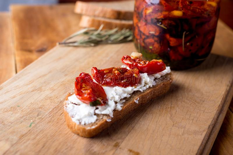 De sandwich met geitkaas, in de zon gedroogde tomaten en thyme, diende op de Raad aan een heldere houten oppervlakte royalty-vrije stock afbeeldingen