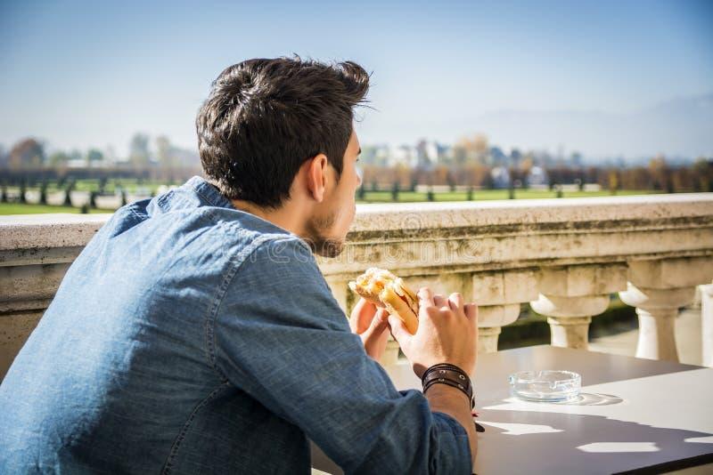 De sandwich van de jonge mensenholding terwijl het zitten in koffie stock afbeeldingen