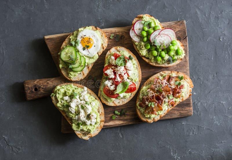 De sandwich van de ontbijtavocado - met knapperig bacon, kwartelsei, tomaten, geitkaas, groene erwten, radijs, komkommer bij het  stock afbeeldingen