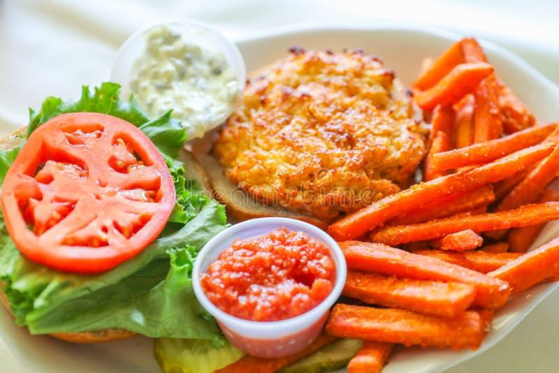 De sandwich van de verse, krabcake met tomatenplakken en bataatgebraden gerechten stock foto