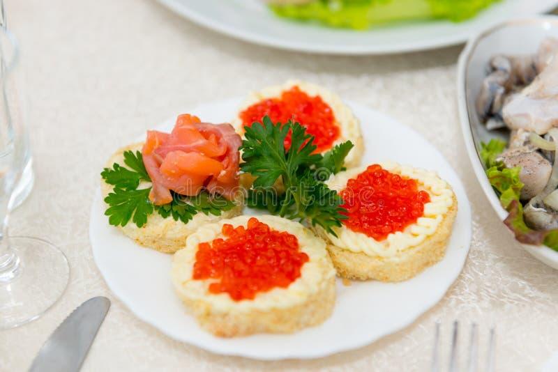 De sandwiches met rode kaviaar en zalm worden dicht omhoog uitgespreid op een plaat op een buffetlijst stock fotografie