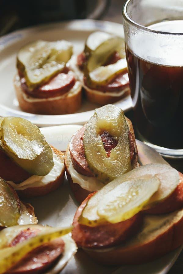 De sandwiches met worst en gezouten komkommer liggen op een plaat stock foto