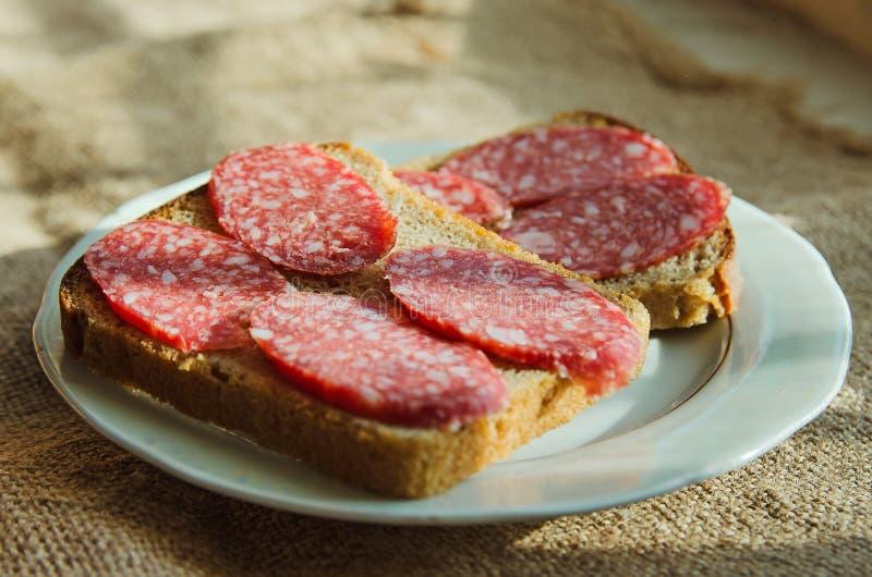 De sandwiches van zwart brood met gerookte worst ligt op een plaat royalty-vrije stock foto's