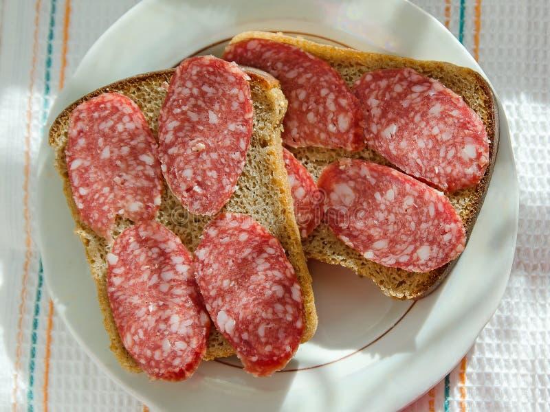 De sandwiches van zwart brood met gerookte worst ligt op een plaat royalty-vrije stock fotografie