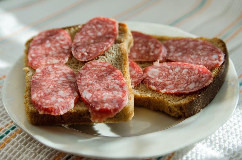 De sandwiches van zwart brood met gerookte worst ligt op een plaat stock afbeeldingen
