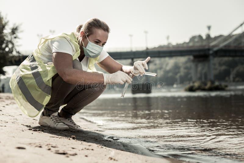 De sanitaire reageerbuizen van de inspecteursholding terwijl het controleren van het niveau van de waterverontreiniging royalty-vrije stock foto