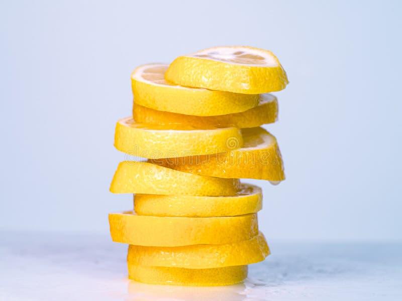 De sappige citroenplakken stapelden zich samen op lichte lijst, dichte omhooggaande mening op De gele citroen cutted in plakken C stock afbeeldingen