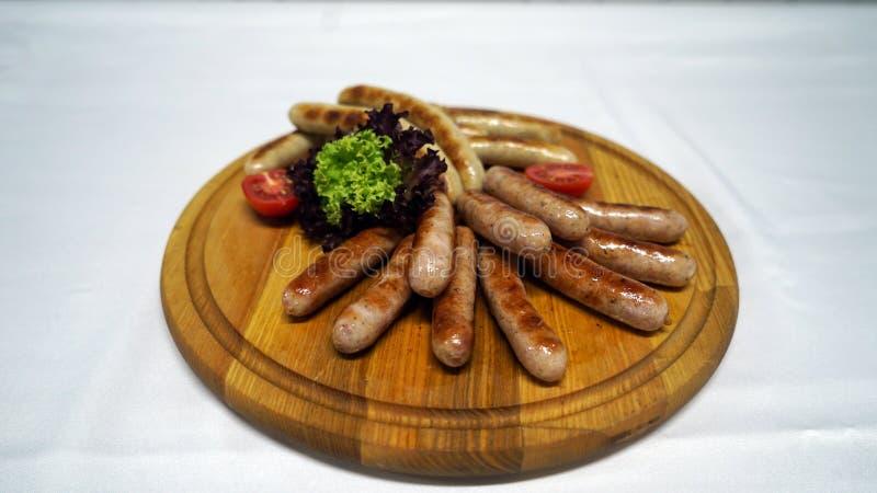 De sappige die worsten op een grill, gebakken korst worden gekookt en dienden met verse groenten op het hout royalty-vrije stock afbeelding