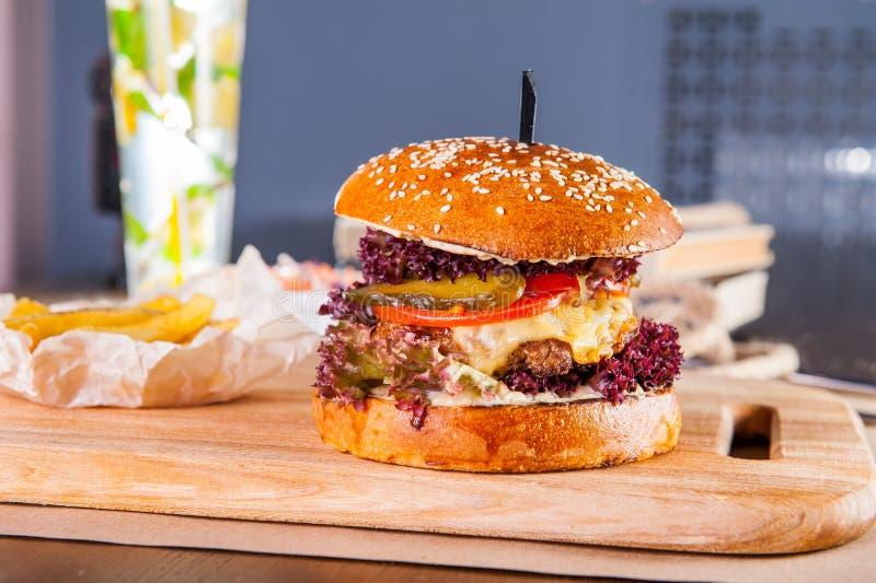 De sappige hamburger met de kotelet van de rundvleeshamburger, ui, sla, groenten in het zuur, tomaten en kaassaus in traditionele stock foto
